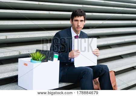 Portrait of young unemployed man looking at camera with sad facial expression while sitting on stairs outdoors after being fired or after business bankruptcy