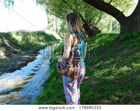 Woman standing watching as the stream flows
