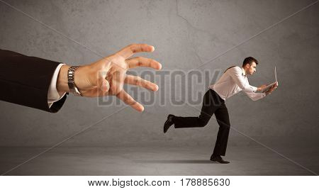 Young miniature businessman running from a big hand with grey background