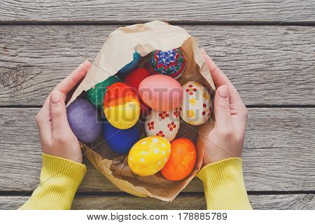 Woman give painted easter eggs on wood background. Colorful handmade holiday decoration on rustic table top view