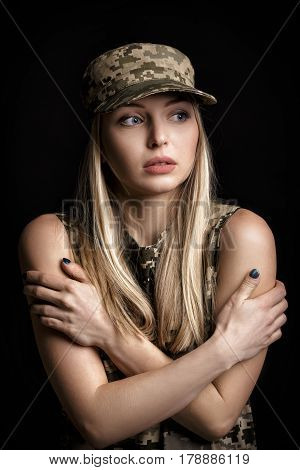 portrait of a beautiful blond woman soldiers in military attire on black background. cold and despair