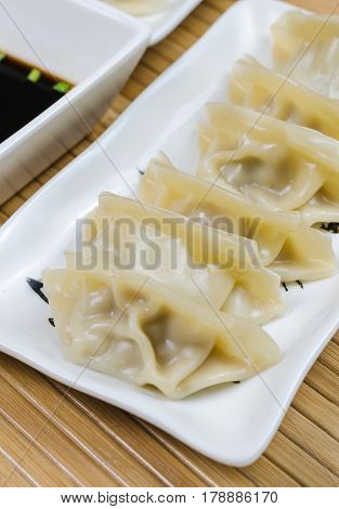 Steamed gyoza dumplings on white plate with soy souse.