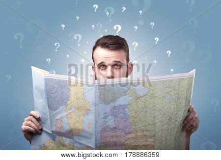 Handsome young man holding a map with white question marks above his head