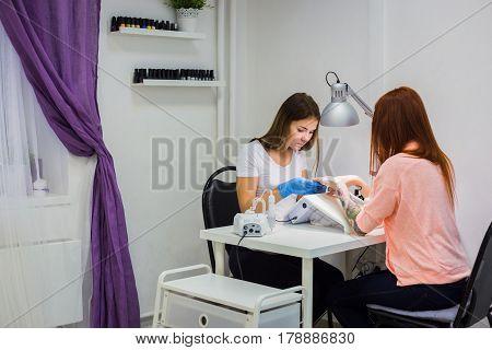 Manicure care procedure, Woman in a nail salon receiving a manicure by a beautician