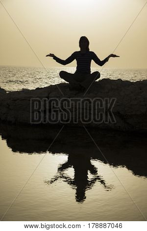 Woman sits as yogi against beautiful sunset over sea background. Only silhouette is seen.