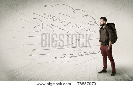 Handsome young man standing with a backpack on his back and scribbles in the background