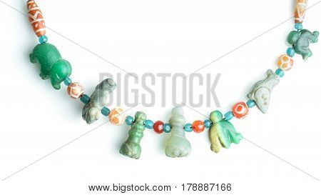 Variety of ancient rare crafted stone beads separated with small etched carnelian beads and turquoise glass beads in necklace isolated on white background