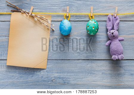 Handmade easter card and garland with painted eggs and bunny on wood background. Colorful holiday decoration on rustic table top view