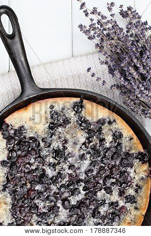 Above image of a blueberry lavender cobbler baked in a cast iron skillet over a white wood table top. Image shot from overhead. Perfect dessert for spring or summer.
