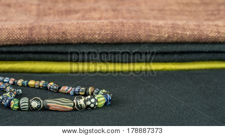 Variety of ancient glass beads in necklace with fabric background