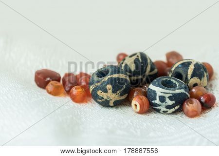 Ancient bird dark blue glass beads together with variety shapes of ancient carnelian beads on offwhite silk cloth