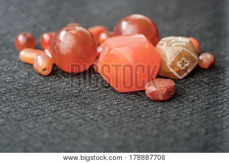 Varieties of ancient carnelian beads on Thai silk background