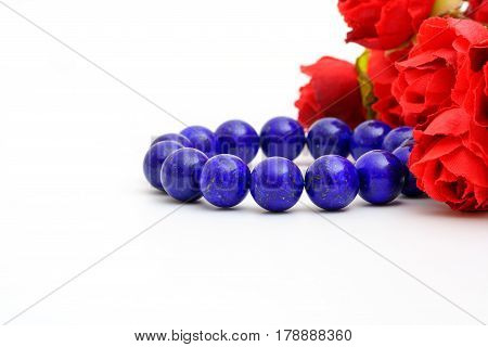 Beautiful high grade royal blue Lapis lazuli beads in bracelet with red roses on white background