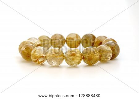 Beautiful translucent golden-yellow color Rutilated Quartz or Venus' hairstone bracelet on white background