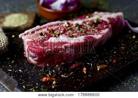 closeup of a raw strip steak seasoned with different spices, such pepper corns of different colors or oregano, on a dark wooden tray, on a table, next to a bowl with chopped purple onion