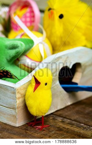 closeup of some some toy chicks and some different decorated easter eggs in a rustic wooden tray, on a wooden surface