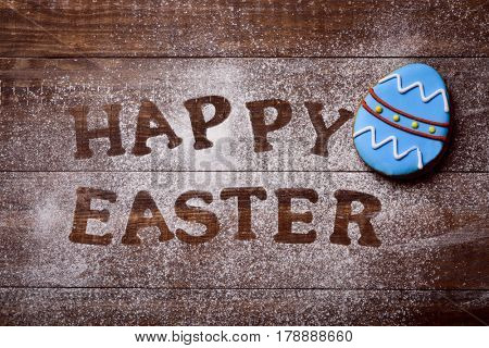 high-angle shot of a wooden table sprinkled with icing sugar or flour where you can read the text happy easter and a cookie decorated as an ornamented easter egg