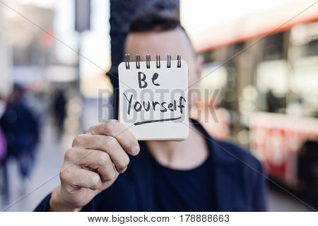 closeup of a young caucasian man in the street showing a notepad with the text be yourself written in it