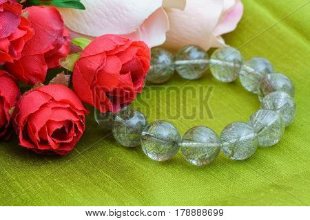 Beautiful natural rare silver Rutile Quartz Gemstone Bead Bracelet with roses on Thai green silk cloth background