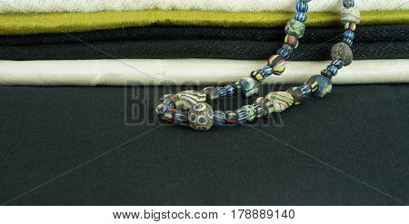 Close up on ancient rare variety of glass beads with variety of silk fabric background