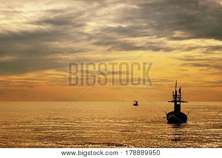 Fishing boat silhouette and sunset ocean background