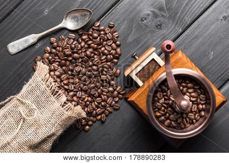 Top View Of Roasted Coffee Beans In Sack, Coffee Grinder And Spoon On Table
