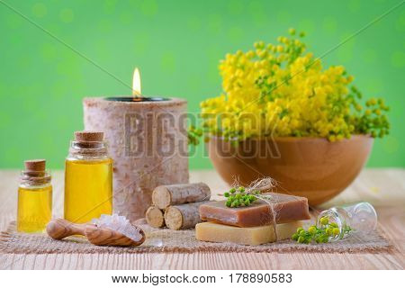wellness, spa and aromatherapy with essential oils, fresh plants, soap, salt on green background