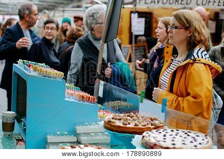 LONDON, UK - MARCH 18, 2017: Woman looking at desserts sold on a market stall in Greenwich Market, London's only market set within a World Heritage Site.