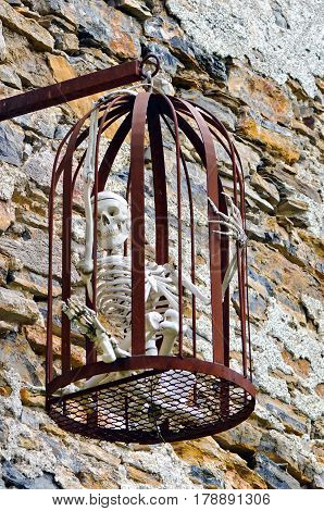 Skeleton model caught in a hanging iron cage.