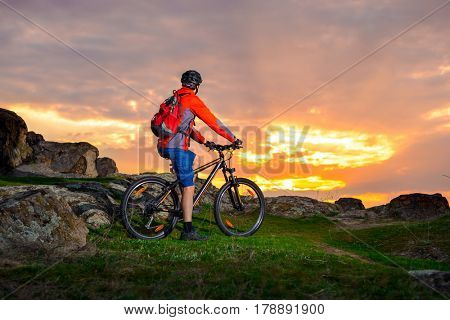 Cyclist with his Mountain Bike Looking at the Beautiful Sunset on the Spring Rocky Trail. Extreme Sports and Adventure Concept.