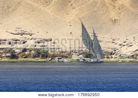 Felucca (river boat) on the Nile with the Sahara behind in Aswan Egipt.