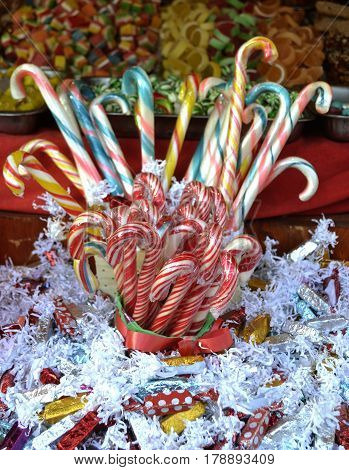 Bunch of candy canes, surrounded by sweets in colorful, glossy covers
