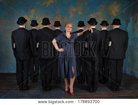 Serious imperious businesswoman leaned against the man's back. Men dressed in suits and in bowlers and are holding a newspaper under their arms. Concept of lady boss.