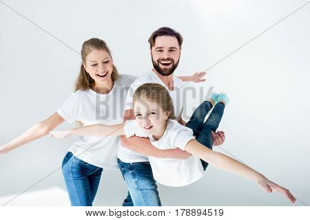 Happy Young Family In White T-shirts And Jeans Having Fun Together