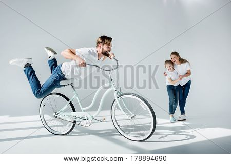 Excited Mother And Daughter Looking At Happy Man Riding Bicycle And Having Fun