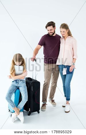 Parents Looking At Upset Daughter With Tablet Sitting On Traveling Bag On White