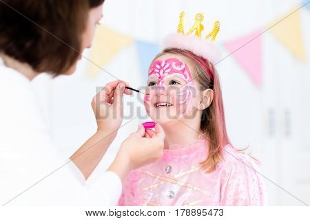 Face painting for little girl. Princess and fairy theme birthday party with face paint artist and costume for preschool child. Kids celebrating Halloween or carnival with pink dress and crown.
