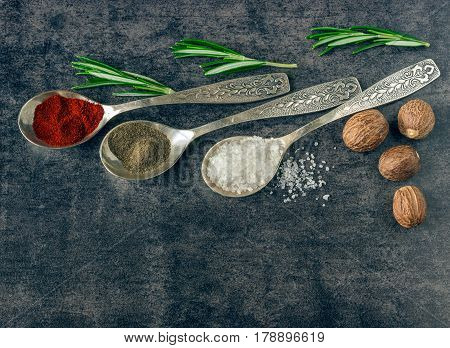 Herbs and spices in metal spoons on a dark background. Ingredients for cooking. Nutmeg.