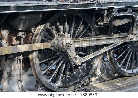 Close up of driving wheels of a vintage steam preparing to move off