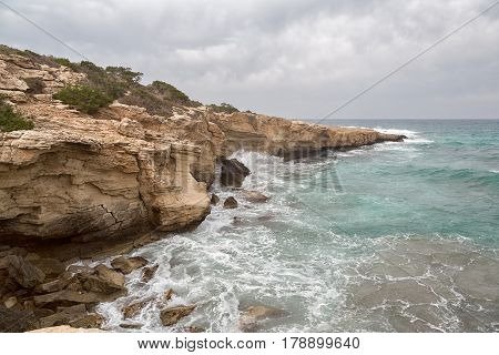 Waves of the Mediterranean Sea break the rocky coastline of the island of Cyprus, on the rocks the white crests of the wave