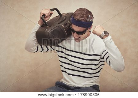 Man with headband listening to music in his boombox