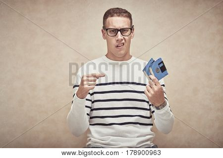 Confused young man pointing at floppy disks in his hand
