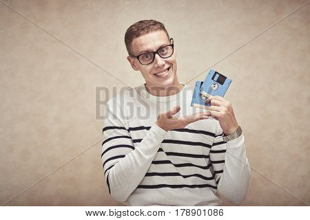 Nerdy smiling man in glasses showing floppy disks