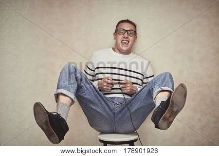 Emotional young man with gamepad in his hands playing on game console