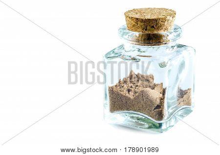 Dry nutmeg powder in glass bottle isolated on white background. Closeup macro shot.