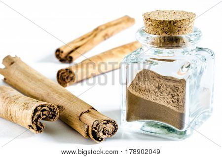Dry cinnamon powder in glass bottle and whole cinnamon sticks near it isolated on white background. Closeup macro shot.