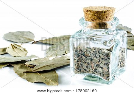 Dry crushed bay leaf in glass bottle and whole bay leaf isolated on white background. Closeup macro shot.