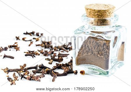 Dry cloves powder in glass bottle and whole cloves near it isolated on white background. Closeup macro shot.