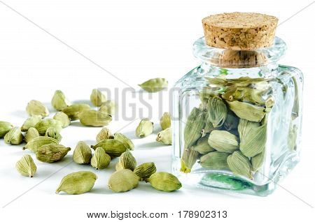 Dry cardamom seeds in glass bottle and heap of cardamom isolated on white background. Closeup macro shot.
