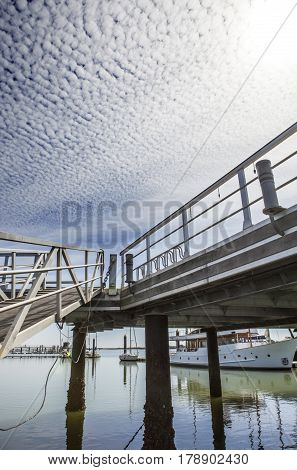 Marina footbridge with cloud formations in the sky called Altocumulus floccus El Rompido Cartaya Huelva Spain